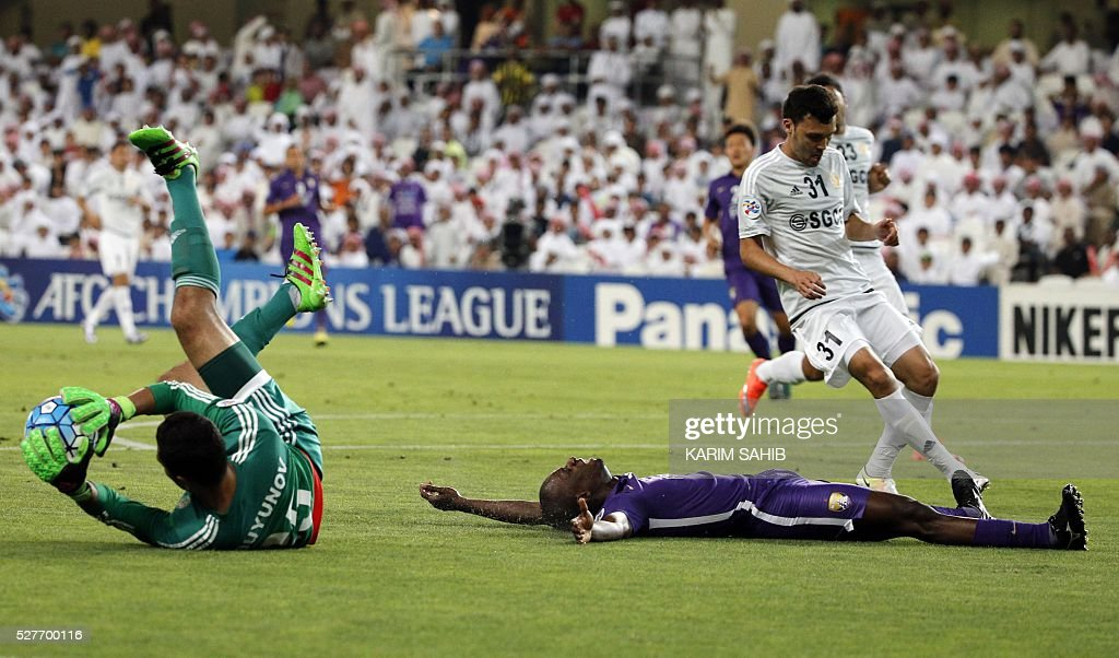 UAE's Al-Ain Danilo Asprilla (R) reacts after failing an attempt to score as Uzbek's Nasaf club goalkeeper Eldorbek Suyunov (L) saves the ball during their Asian Champions League group D football match at the Hazza bin Zayed Stadium in Al-Ain on May 3, 2016. / AFP / KARIM