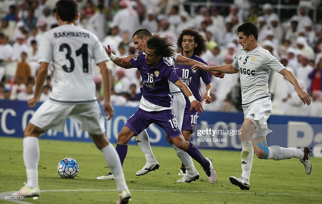 UAE's Al-Ain player Mohamed Al-Raqi (C) dribbles the ball between Uzbek's Nasaf club players Rakhmatov Saidulla (L) and Mamatkazin Ildar during their Asian Champions League group D football match at the Hazza bin Zayed Stadium in Al-Ain on May 3, 2016. / AFP / KARIM
