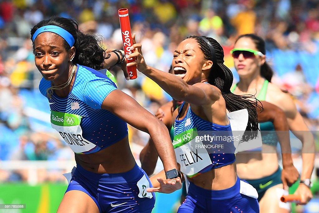 TOPSHOT USA's Allyson Felix hands the baton to USA's English Gardner competes in the Women's 4 x 100m Relay Round 1 during the athletics event at the...