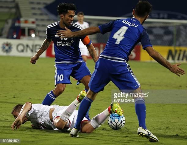 UAE's AlNasr club players Luis Jimenez and Khalid Jalal react as Uzbekistan's Lokomotiv club player Server Djeparov falls to the ground during their...