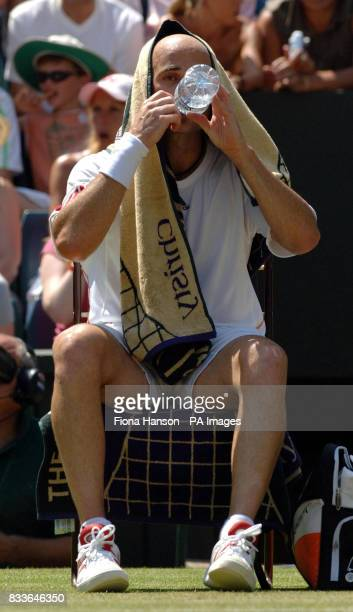 USA's Andre Agassi covers his head with a towel against Spain's Rafael Nadal during the third round of The All England Lawn Tennis Championships at...
