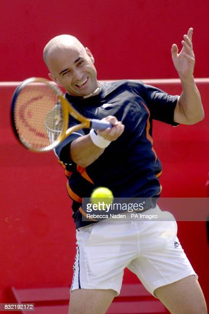 USA's Andre Agassi serves Great Britain's Tim Henman during the first round match of The Stella Artois Championships at The Queen's Club London