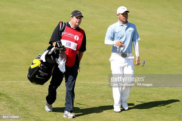 USA's Anthony Kim walks down the fairway with his caddie