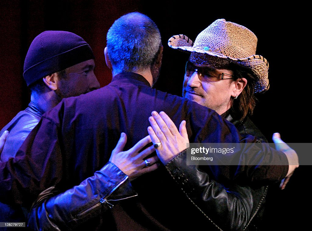 U2's <a gi-track='captionPersonalityLinkClicked' href=/galleries/search?phrase=Bono+-+Singer&family=editorial&specificpeople=167279 ng-click='$event.stopPropagation()'>Bono</a>, right, and The Edge, left, hug <a gi-track='captionPersonalityLinkClicked' href=/galleries/search?phrase=Steve+Jobs&family=editorial&specificpeople=204493 ng-click='$event.stopPropagation()'>Steve Jobs</a>, chief executive officer and co-founder of Apple Inc., center, during an event in San Jose, California, U.S., on Tuesday, Oct. 26, 2004. Jobs, who built the world's most valuable technology company by creating devices that changed how people use electronics and revolutionized the computer, music and mobile-phone industries, died Wednesday, Oct. 5, 2011. He was 56. Photographer: Noah Berger/Bloomberg via Getty Images