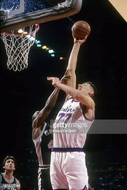 BALTIMORE MD CIRCA 1990's Center Gheorghe Muresan of the Washington Bullets shoots over a San Antonio Spurs defender circa mid 1990's during an NBA...
