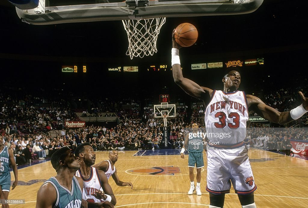 MANHATTAN, NY - CIRCA 1990's: Center Patrick Ewing #33 of the New York Knicks in action pulls down a rebound against the Charlette Hornets circa early 1990's during an NBA basketball game at Madison Square Garden in Manhattan, New York. Ewing played for the Knicks from 1985-00.