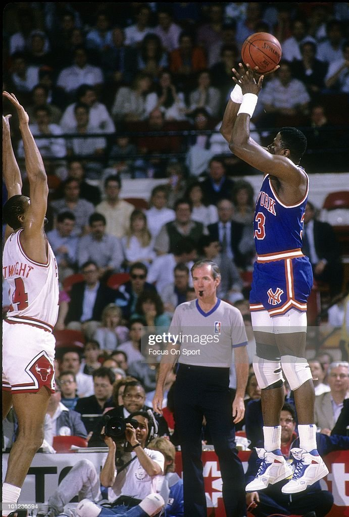 CHICAGO, IL - CIRCA 1990's: Center Patrick Ewing #33 of the New York Knicks in action shoots over center Bill Cartwright #24 of the Chicago Bulls circa early 1990's during an NBA basketball game at the United Center in Chicago, Illinois. Ewing played for the Knicks from 1985-00.