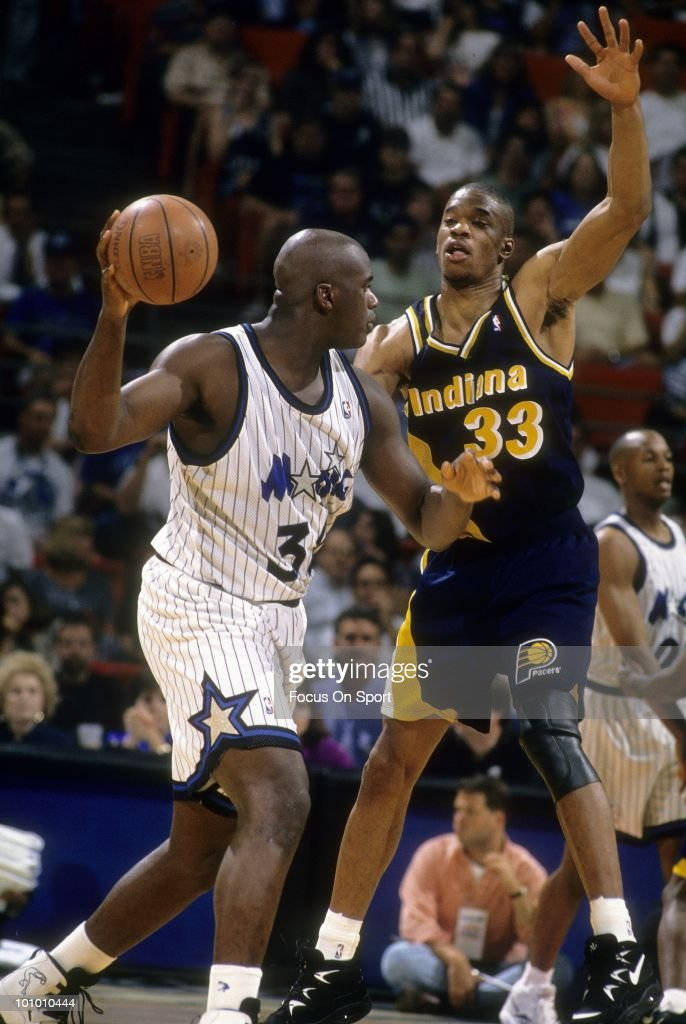 ORLANDO FL CIRCA 1990's Center Shaquille O'Neal of the Orlando Magic is guarded by center Antonio Davis of the Indiana Pacers circa mid 1990's during...