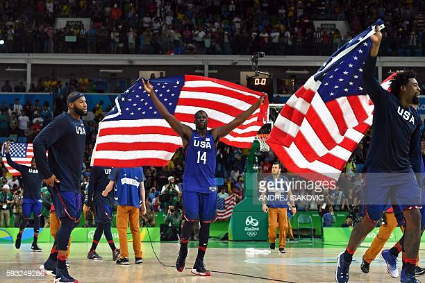 USA's centre DeMarcus Cousins USA's forward Draymond Green and USA's centre DeAndre Jordan celebrate with USA's flags after defeating Serbia during a...
