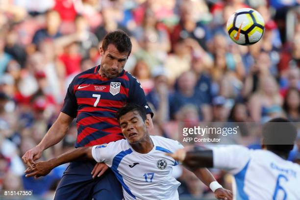 USA's Chris Pontius left heads the ball away from Nicaragua's Bismarck Veliz during the first half of a CONCACAF Gold Cup soccer match in Cleveland...