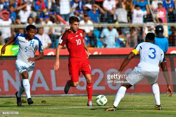 USA's Christian Pulisic is marked by Honduras' Ever Alvarado and Maynor Figueroa during their 2018 World Cup qualifier football match in San Pedro...