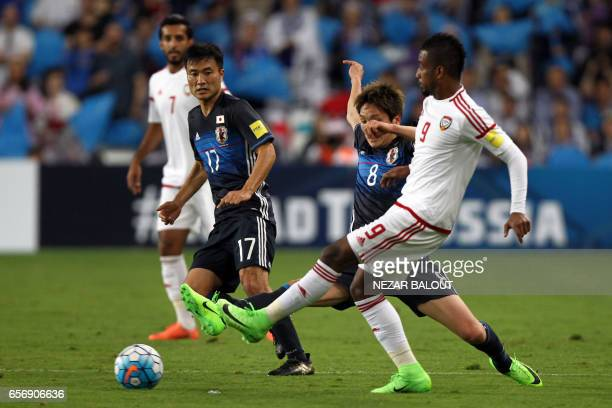 UAE's defender Abdulaziz Hussain Haikal passes the ball as he is marked by Japan's forward Genki Haraguchi during the FIFA World Cup 2018 qualifier...