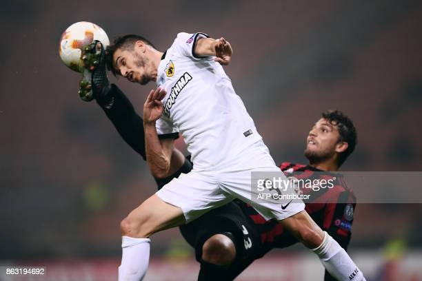 TOPSHOT AEK's defender Helder Lopes from Portugal jumps for the ball with AC Milan's midfielder Manuel Locatelli the UEFA Europa League football...