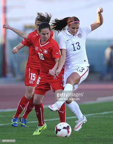 US's forward Alex Morgan vies with Switzerland's defender Fabienne Humm during the Algarve Cup football match USA vs Switzerland at the Estadio...