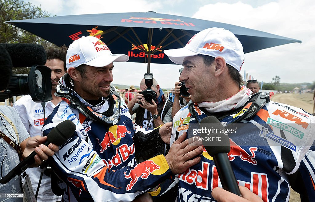 KTM's French biker Cyril Despres (L) congratulates KTM's Portuguese rider Ruben Faria after the 14th stage of the Dakar 2013, between La Serena and Santiago, Chile on January 19, 2013. KTM's French biker Cyril Despres won the Dakar 2013 ahead of KTM's Portuguese rider Ruben Faria and KTM's Chilean rider Francisco Chaleco Lopez. AFP PHOTO / FRANCK FIFE