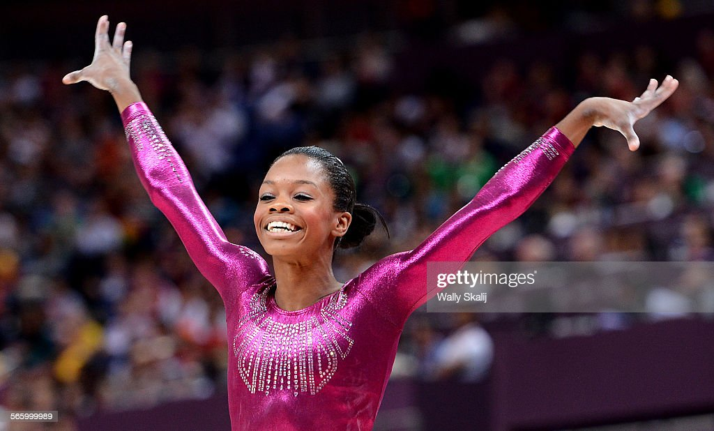 USA's Gabrielle Douglas is all smiles after competing on the beam and on her way to winning the gold medal in the women's individual all–around at...