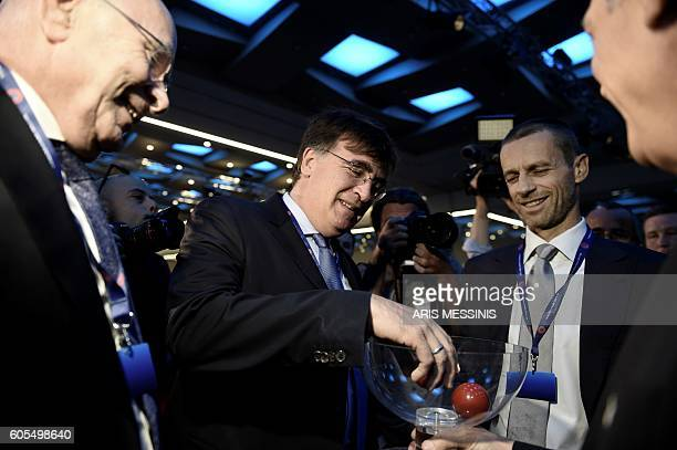 UEFA's general secretary Theodore Theodoridis picks a draw ball next to presidential candidates Michael van Praag and Aleksander Ceferin during the...