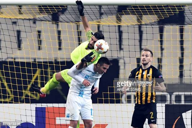 AEK's goalkeeper Giannis Anestis stops a ball as he is challenged by Rijeka's Mario Gavranovic during the UEFA Europa League Group D football match...