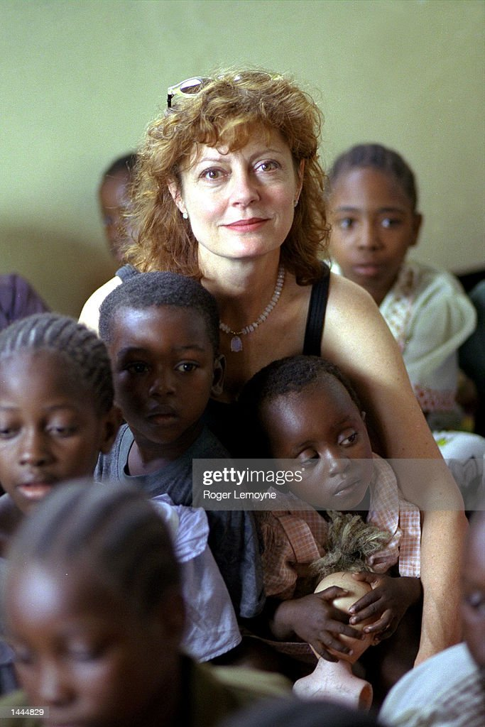 UNICEF''s Goodwill Ambassador Susan Sarandon sits amidst a group of children May, 2000 and watches a song and dance performance by children at the UNICEF-assisted Kiwohede drop in centre for destitute children in Dar-es-Salaam, Tanzania. Sarandon''s visit to Tanzania from May 18-21, 2000 is her first visit on behalf of UNICEF since her appointment in 1999 to promote increased awareness about AIDS both within the country and to help draw world attention to the African AIDS crisis in general.