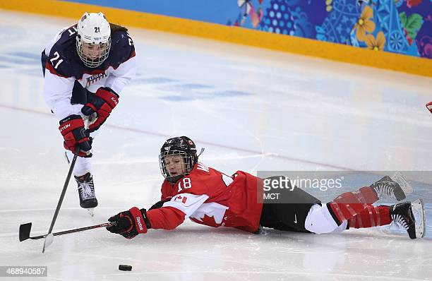 USA's Hilary Knight and Canada's Catherine Ward chase the puck in the second period of a women's hockey game at the Winter Olympics in Sochi Russia...