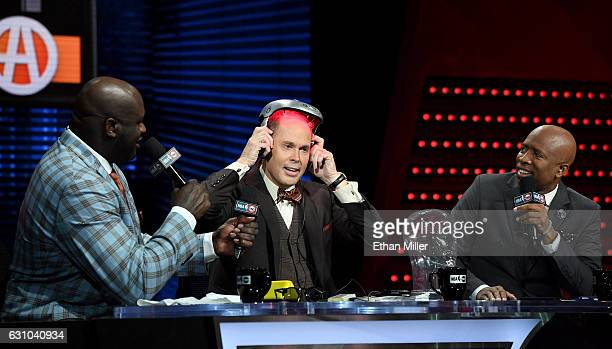 TNT's Inside the NBA host Ernie Johnson Jr puts on an iGrow laserbased hairgrowth helmet as NBA analysts Shaquille O'Neal and Kenny Smith look on...