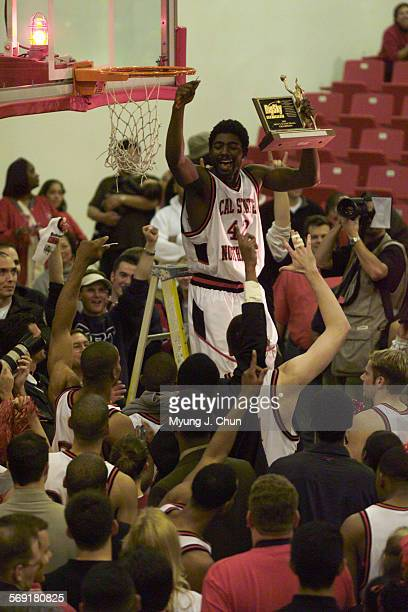 CSUN's Jeff Parris shows off the team's Big Sky trophy before cutting off a souvenir piece of the net DIGITAL IMAGE SHOT ON SATURDAY 3/10/2001