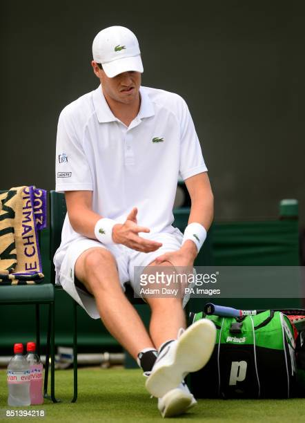 USA's John Isner struggles with an injury before retiring form his match against France's Adrian Mannarino during day Three of the Wimbledon...