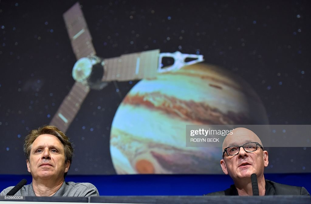 NASA's Juno Mission Principal Investigator Scott Bolton (L) and Robert Kondrk (R), Apple vice president for Content and Media Apps, speak at a press conference at the Jet Propulsion Laboratory in Pasadena, California, June 30, 2016 to announce 'Destination: Juno,' a collaboration between NASA and Apple to bring 'exploratory' music inspired by space from artists such as Brad Paisley, Corinne Bailey Rae, GZA, Jim James featuring Lydia Tyrell, Trent Reznor & Atticus Ross, Weezer and Zoé to Apple Music and iTunes listeners. The Juno spacecraft is scheduled to enter Jupiter's orbit on July 4, 2016 after a five years voyage to the fifth planet from the sun. / AFP / Robyn Beck