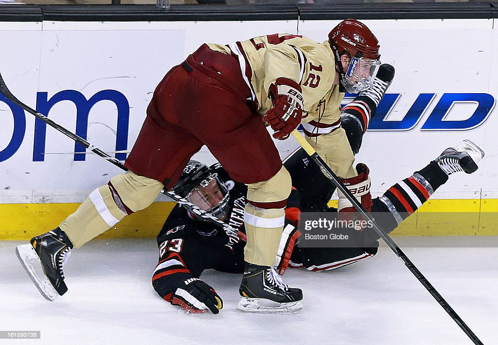 BC's Kevin Hayes (#12) sends NU's Colton Saucerman to the ice during first period action. Boston College and Northeastern University met in the championship game of the Beanpot Tournament at the TD Garden.