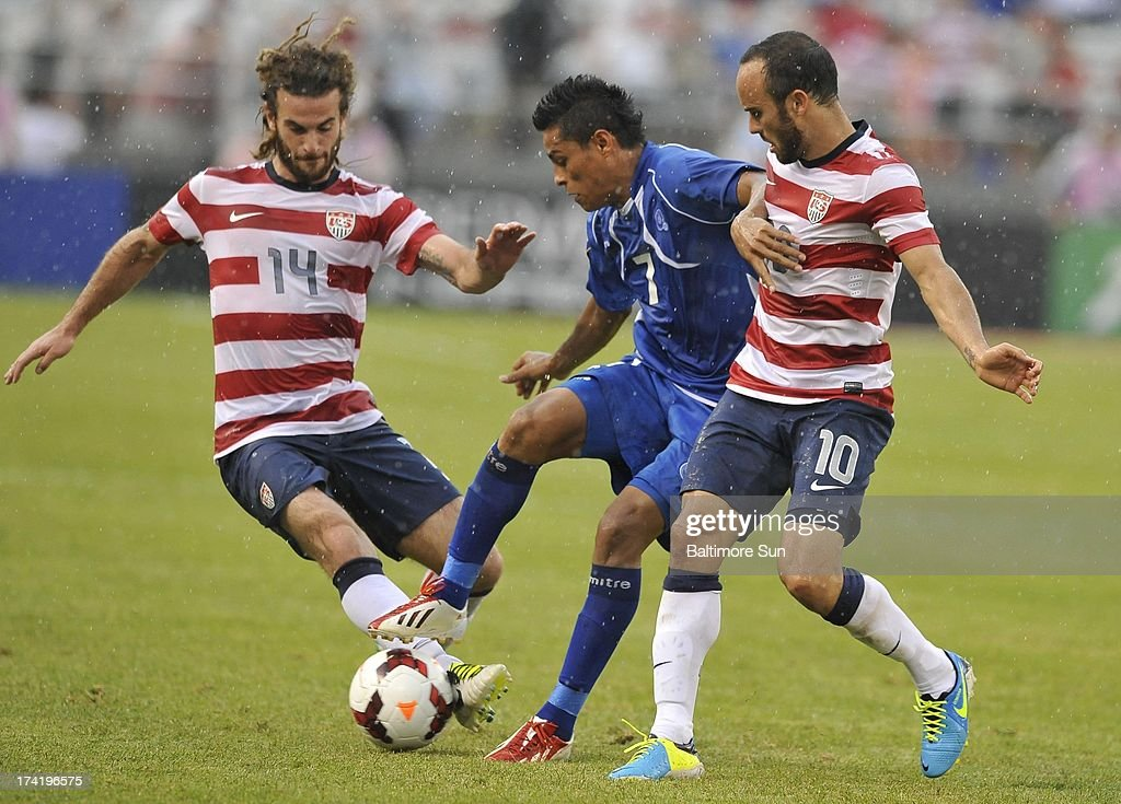 U.S.'s Kyle Beckerman gets a foot on the ball as El Salvador's Darwin Ceren Delgado holds off U.S.'s Landon Donovan during the second half of the Gold Cup quarterfinals in Baltimore, Maryland, Sunday, July 21, 2013. U.S. wins, 5-1.