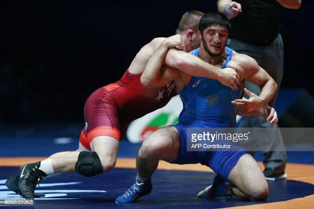 USA's Kyle Snyder challenges Russia's Abdulrashid Sadulaev during the men's freestyle wrestling 97kg category final at the FILA World Wrestling...
