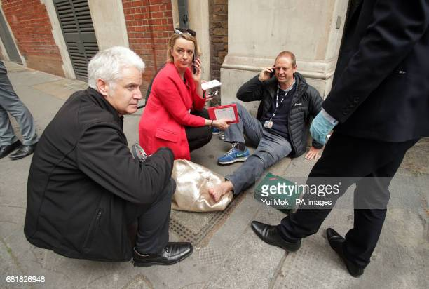 BBC's Laura Kuenssberg on the phone while her colleague BBC cameraman Giles Wooltorton sits on the floor after the car carrying Jeremy Corbyn ran...