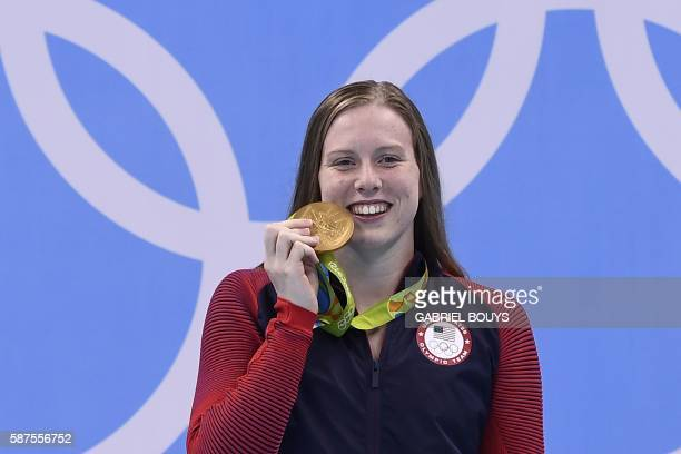 USA's Lilly King bites her gold medal on the podium after she won the Women's 100m Breaststroke Final during the swimming event at the Rio 2016...