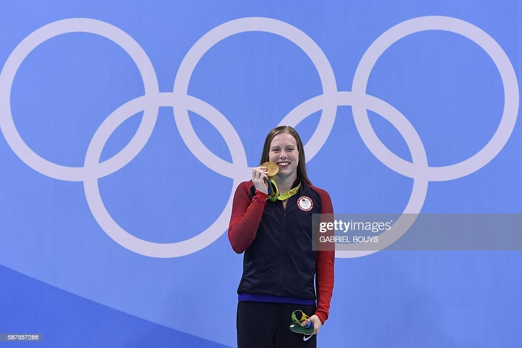 USA's Lilly King bites her gold medal on the podium after she won the Women's 100m Breaststroke Final during the swimming event at the Rio 2016 Olympic Games at the Olympic Aquatics Stadium in Rio de Janeiro on August 8, 2016. / AFP / GABRIEL