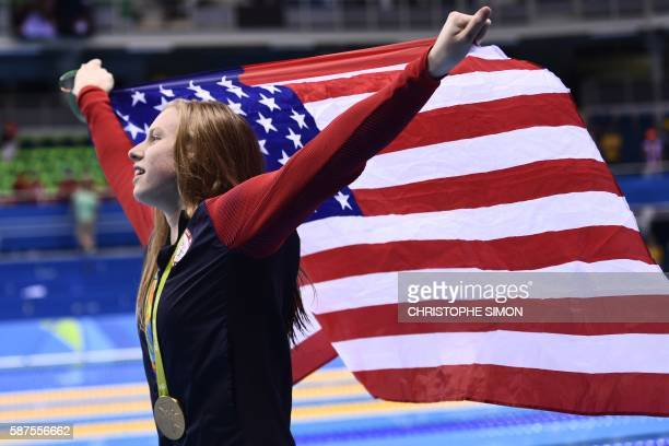TOPSHOT USA's Lilly King waves her national flag on the podium after she won the Women's 100m Breaststroke Final during the swimming event at the Rio...
