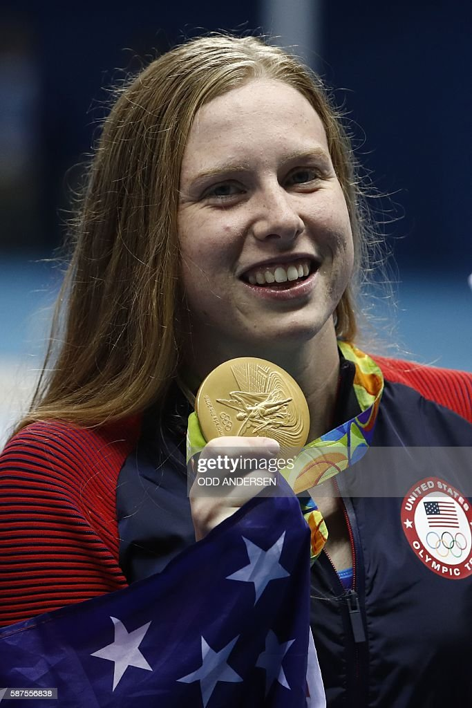 USA's Lilly King wrapped in her national flag poses with her gold medal on the podium after she won the Women's 100m Breaststroke Final during the swimming event at the Rio 2016 Olympic Games at the Olympic Aquatics Stadium in Rio de Janeiro on August 8, 2016. / AFP / Odd Andersen