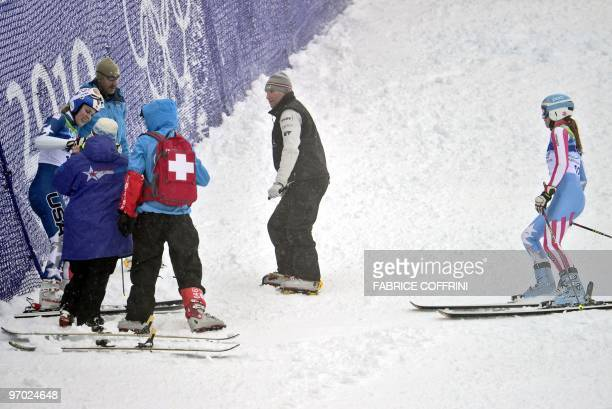 USA's Lindsey Vonn is helped by medics and coaches after crashing as USA's Julia Mancuso looks on during the Women's Vancouver 2010 Winter Olympics...