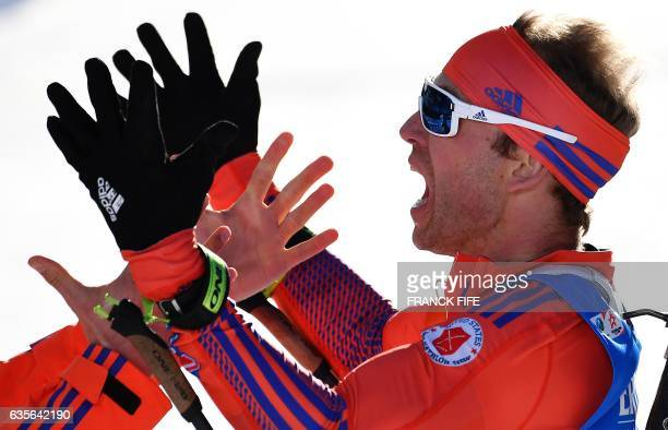 TOPSHOT US's Lowell Bailey celebrates in the finish area with a staff member after the Men 20 km Individual event at the FIS Biathlon World...