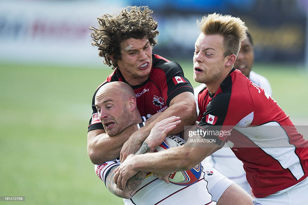USA's Luke Hume is tackled by Canada's Taylor Paris (L) and Harry Jones during Day 3 of the USA Sevens Las Vegas HSBC Sevens World Series Round 5 at Sam Boyd Stadium in Las Vegas, NV, February 10, 2013. AFP PHOTO/Jim WATSON
