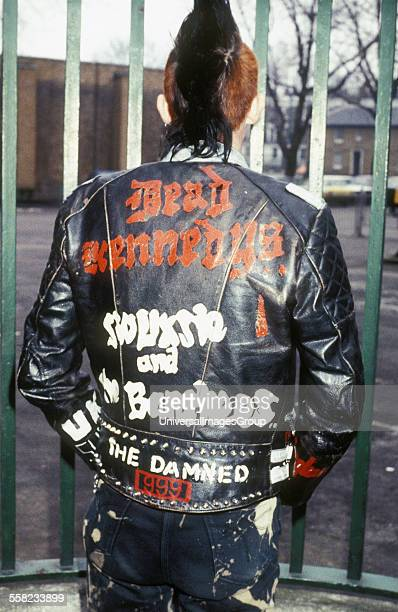 80's Male Punk wearing 'dead kennedy's' leather jacket standing in front of gate UK 1980's