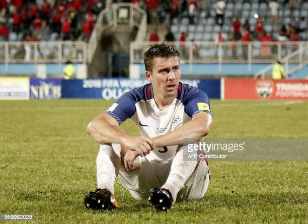 USA's Matt Besler sits on the field in dejection after losing to Trinidad and Tobago 21 in a qualifier match and missing the 2018 World Cup in Couva...