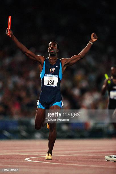 USA's Michael Johnson raises his arms as he crosses the finish line to win the 4x400meter relay final at the Sydney Olympic Games