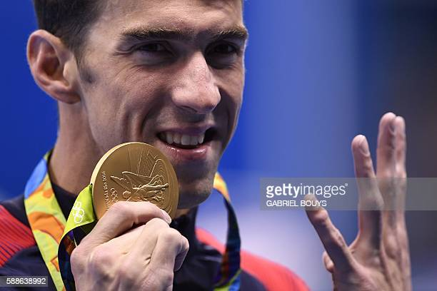 TOPSHOT USA's Michael Phelps holds up four fingers for his fourth gold medal on the podium of the Men's 200m Individual Medley Final during the...
