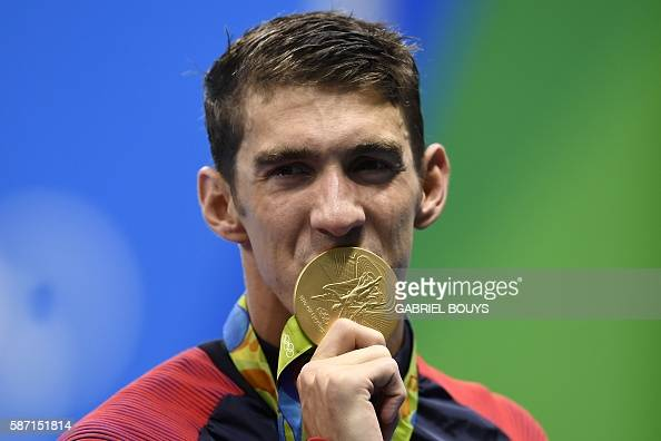 TOPSHOT USA's Michael Phelps kisses his gold medal on the podium of the Men's 4x100m Freestyle Relay Final during the swimming event at the Rio 2016...
