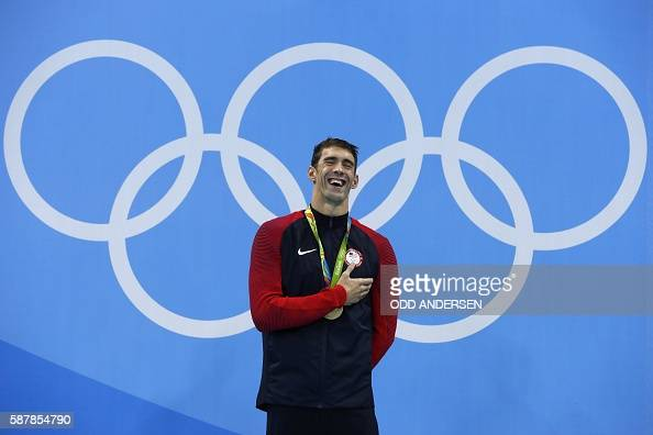 USA's Michael Phelps laughs on the podium with his gold medal after he won the Men's 200m Butterfly Final during the swimming event at the Rio 2016...