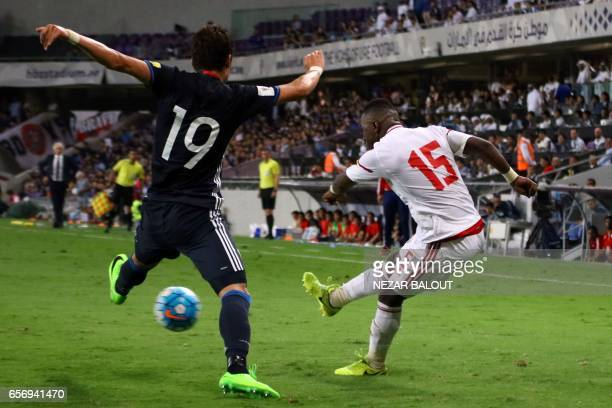 UAE's midfielder Ismail Al Hammadi crosses the ball as he is marked by Japan's defender Hiroki Sakai during the FIFA World Cup 2018 qualifier between...