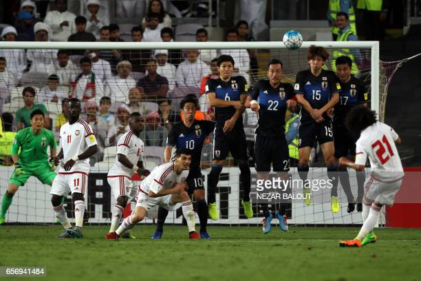 UAE's midfielder Omar Abdulrahman curls a freekick over the Japan's players during the FIFA World Cup 2018 qualifier between UAE and Japan at Hazza...