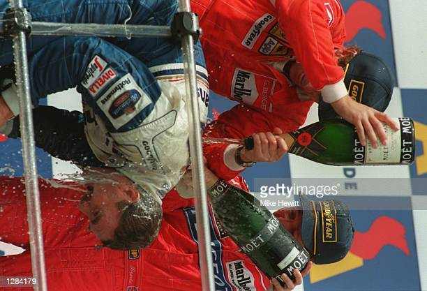 BRITAIN's NIGEL MANSELL IS SOAKED WITH CHAMPAGNE BY FERRARI's GERHARD BERGER MCCLAREN's MARTIN BRUNDLE AFTER WINNING THE AUSTRALIAN GRAND PRIX IN...