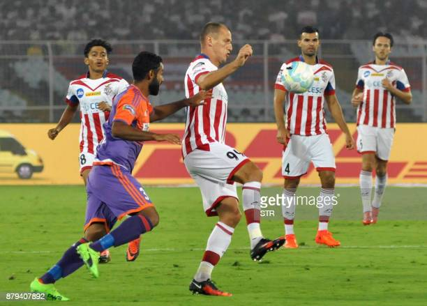 ATK's Njazi Kuqi vies for the ball with FC Pune City's Gurtej Singh during the Indian Super League football match between ATK and FC Pune City at The...