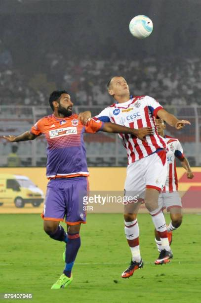 ATK 's Njazi Kuqi vies for the ball with FC Pune City's Gurtej Singh during the Indian Super League football match between ATK and FC Pune City at...